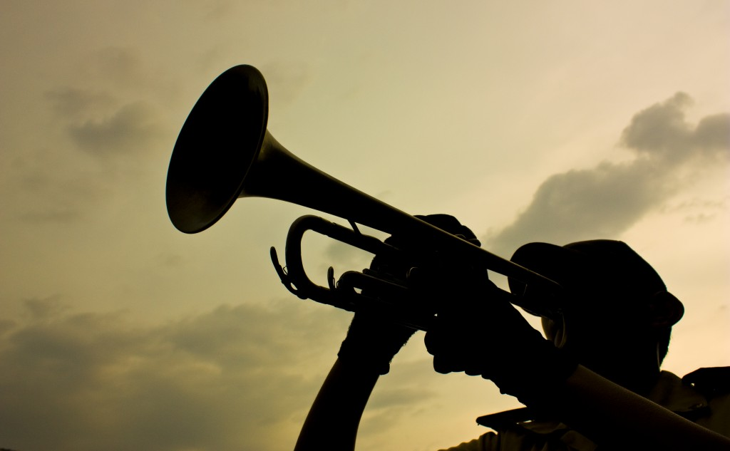 Silhouette of a man playing the bugle against the light sky