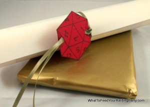 Small gift wrapped in gold tissue with a scroll card tied with ribbon and a paper D20 tag